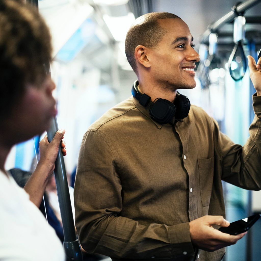 man on a train with headphones around his neck